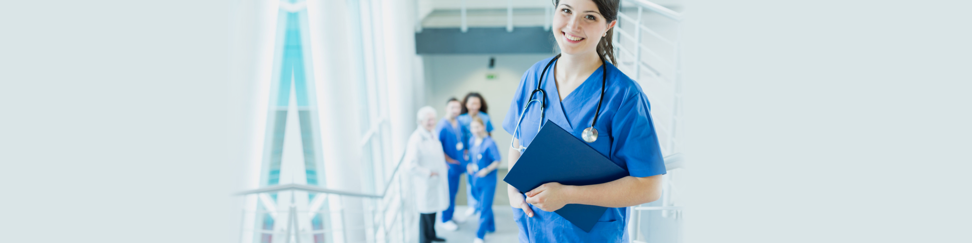 Happy, young woman in blue uniform during medical internship at a hospital